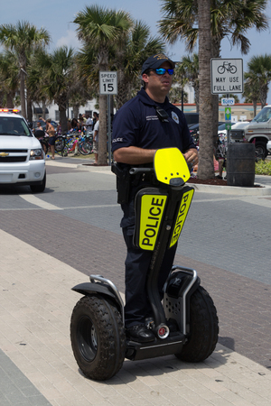 officially: JACKSONVILLE BEACH, FL - APRIL 27, 2014: A police officer on a Segway during the 68th annual Opening of the Beaches Parade in Jacksonville Beach, Florida. Each year the city holds a parade to officially open the beaches for the summer months.