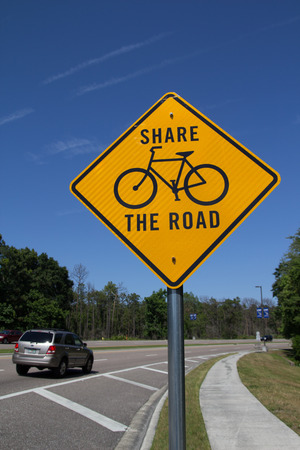 road bike: JACKSONVILLE, FL - MAY 20, 2014: A black and yellow bike sign in Jacksonville. Fabrication and installation of Share the Road signs range from $200 to $225 each.