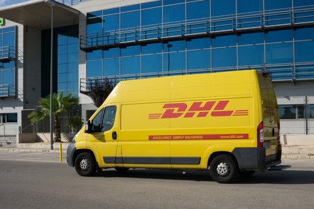VALENCIA, SPAIN - JUNE 13, 2014: A DHL delivery van on the street in Valencia. DHL is a world wide courier company that operates in 220 countries with over 285,000 employees. Stock Photo - 29099907