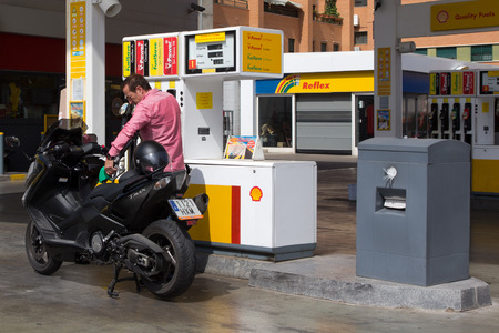 VALENCIA, SPAIN - JUNE 10, 2014: A man filling up his scooter at a Shell gas station in Valencia. According to Forbes, Royal Dutch Shell oil company is the 5th largest company worldwide.