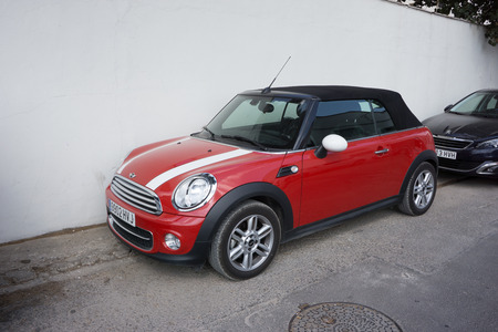 voted: VALENCIA, SPAIN - AUGUST 20, 2014: Mini Cooper Convertible car parked in the street in Valencia, Spain.  In 1999 the Mini was voted the second most influential car of the 20th century, behind the Ford Model T. Editorial