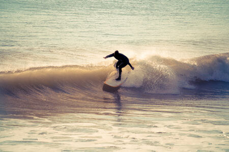Surfing in the early morning with retro effect applied.