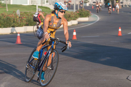 Valencia, Spain - September 6, 2014: Athlete competing in the cycling section of the Womems Toro Loco Valencia Triathlon.