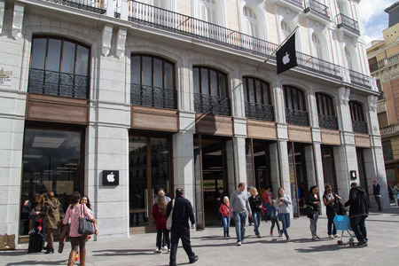 exiting: MADRID, SPAIN - OCTOBER 9, 2014: People entering and exiting the new Apple Store in Madrid. Located in the Puerta de Sol Plaza, the store opened on June 21, 2014.