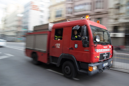 MADRID, SPAIN - OCTOBER 10, 2014: A fire truck speeding through the streets of Madrid. Due to Spanish law, only police use blue lights and ambulances and fire engines have to use amber lights. Stock fotó - 32633564