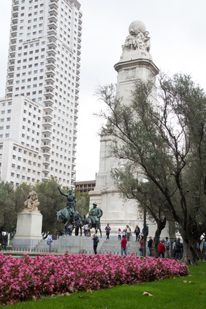 MADRID, SPAIN - OCTOBER 11, 2014: Tourist visiting the famous Don Quixote and Sancho Panza statue in Madrid. The monument is located in the Plaza de España on the western end of the Gran Via.
