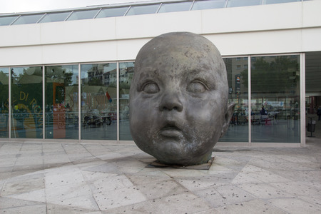 weighs: MADRID, SPAIN - OCTOBER 9, 2014: Baby Head Statue at the Atocha Train Station in Madrid. Created by Artist Antonio Lopez, the statue stands 3 meters high, made of bronze and weighs 2,000 kilos.