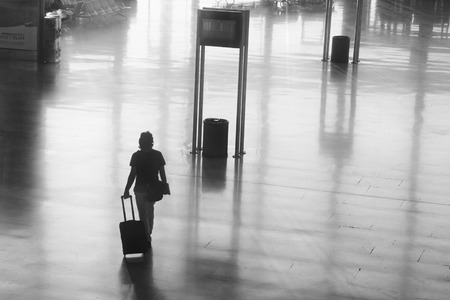 VALENCIA, SPAIN - OCTOBER 26, 2014: An airline passenger walking inside the Valencia Airport.  About 4.98 million passengers passed through the Valencia Airport in 2013.