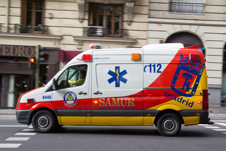 MADRID, SPAIN - OCTOBER 9, 2014: An ambulance speeding through the streets of Madrid. Due to Spanish law, only police use blue lights and ambulances and fire engines have to use amber lights. Editorial
