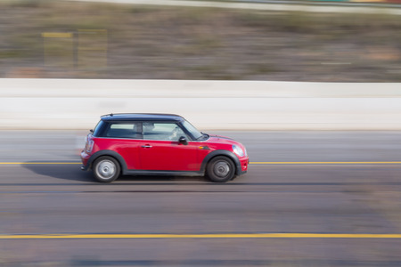 cooper: VALENCIA, SPAIN - NOVEMBER 7, 2014: A red Mini Cooper auto on the highway in Valencia. The Mini Cooper is a popular compact vehicle with a total of 301,526 Mini vehicles sold worldwide in 2012. Editorial