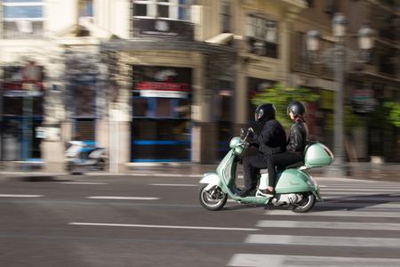 vespa piaggio: VALENCIA, SPAGNA - 16 novembre 2014: Una coppia su uno scooter Vespa in viaggio nel centro della città di Valencia con motion blur. Vespa è un marchio italiano scooter prodotto da Piaggio. Il nome significa vespa in italiano.