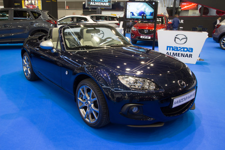 seater: VALENCIA, SPAIN - DECEMBER 4, 2014:  A blue 2014 Mazda MX-5 Miata Convertible at the Valencia Automovil 2014 Car Show. The MX-5  is the best selling two seat convertible sports car in history.