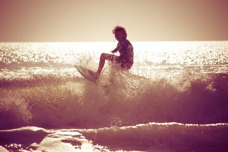 early summer: Surfing in the early morning with retro effect applied.