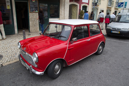 influential: LISBON, PORTUGAL - MAY 28, 2014: A Classic Mini Cooper car parked in the street in Lisbon.  In 1999 the Mini was voted the second most influential car of the 20th century, behind the Ford Model T.