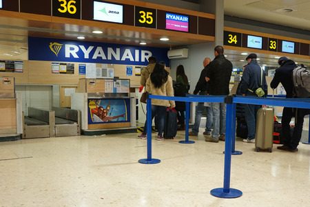 scheduled: VALENCIA, SPAIN - FEBRUARY 14, 2015: Passengers at a Ryanair check-in counter at the Valencia airport. In 2014, Ryanair was the largest European airline by scheduled passengers carried.