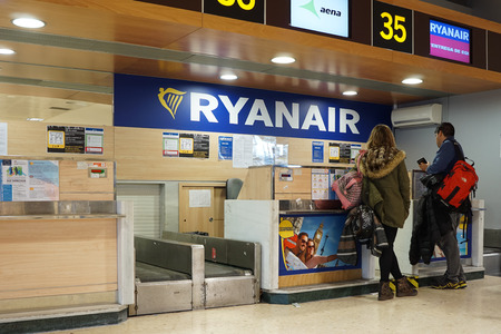 checkin: VALENCIA, SPAIN - FEBRUARY 14, 2015: Passengers at a Ryanair check-in counter at the Valencia airport. In 2014, Ryanair was the largest European airline by scheduled passengers carried.