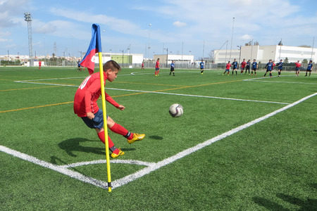 soccer shoes: VALENCIA, SPAIN - APRIL 6, 2015: An unknown youth soccer player taking a corner kick at a city league soccer match. Soccer is the number one sport in Spain.