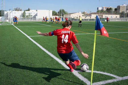 corner kick soccer: VALENCIA SPAIN  MAy 2 2015: An unknown woman soccer player taking a corner kick during a city league soccer match. Soccer is the most popular sport in Spain.