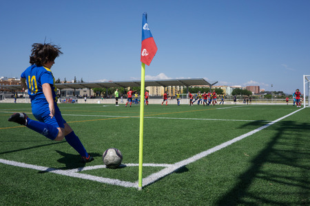 corner kick soccer: VALENCIA SPAIN  MAY 23 2015: An unknown youth soccer player taking a corner kick during a youth city league soccer match. Soccer is the most popular sport in Spain.