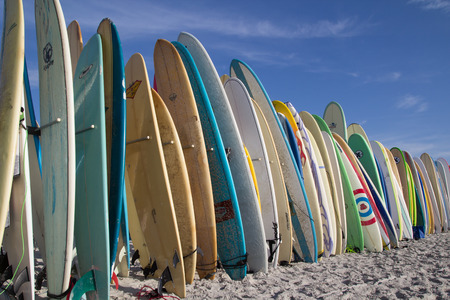 involves: JACKSONVILLE BEACH, FL. USA - JUNE 6, 2015: Surfboards are staged for the Ocean Paddle part of the Never Quit Trident event which involves a 5k Run, 500M Ocean Swim and 1.5k Ocean Paddle. Editorial