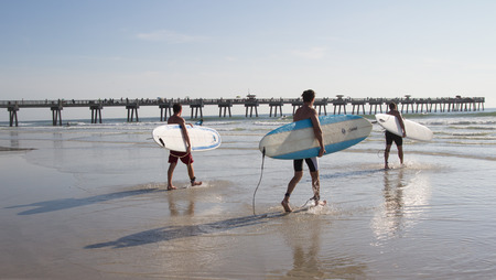 involves: JACKSONVILLE BEACH, FL. USA - JUNE 6, 2015: Unknown athletes begin the Ocean Paddle part of the Never Quit Trident event which involves a 5k Run, 500M Ocean Swim and 1.5k Ocean Paddle.
