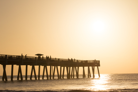 Fishing pier on the beach during the early morning.