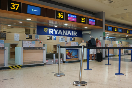 scheduled: VALENCIA, SPAIN - SEPTEMBER 12, 2015: Passengers at a Ryanair check-in counter at the Valencia airport. In 2014, Ryanair was the largest European airline by scheduled passengers carried.