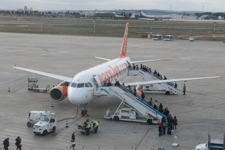 carried: VALENCIA, SPAIN - JANUARY 2, 2016: Passengers boarding an EasyJet airliner at the Valencia Airport. EasyJet is a British airline carrier that is the largest airline of the UK based on the number of passengers carried. Editorial