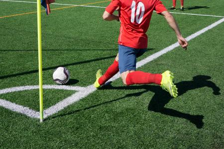 patada: Un jugador de fútbol teniendo un saque de esquina durante un partido de la liga de fútbol de la ciudad. Foto de archivo