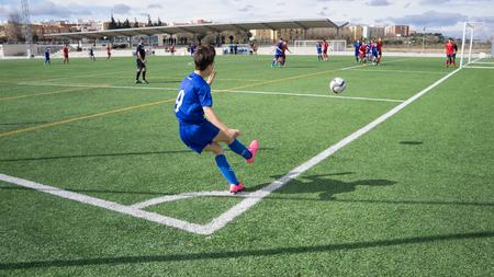 patada: Valencia, España - 13 febrero 2016: Un jugador de fútbol juvenil desconocido realiza un saque de esquina durante un partido de la liga de fútbol juvenil.