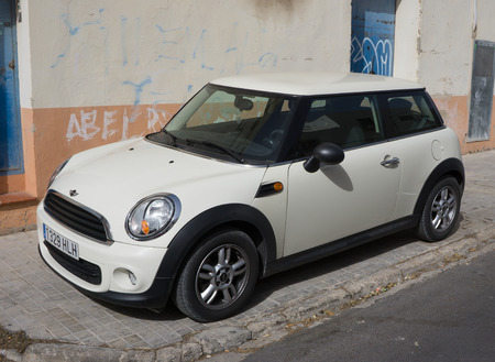 voted: VALENCIA, SPAIN - FEBRUARY 22, 2016: A White Mini Cooper car parked in the street in Valencia, Spain. In 1999 the Mini was voted the second most influential car of the 20th century, behind the Ford Model T.