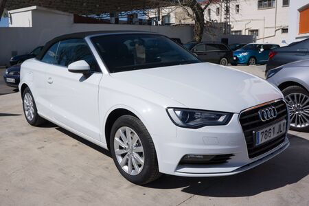 wor: VALENCIA, SPAIN - MARCH 8, 2016: A White 2014 Audi T3 Cabriolet parked in the streets of Valencia. The Audi T3 Cabriolet has an electrically folding canvas roof that stows behind the rear seats. Audi is among the best-selling luxury automobiles in the wor