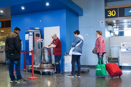 cling: VALENCIA, SPAIN - APRIL 30, 2016: An airline passenger having his luggage wrapped in industrial strength cling film. Wrapping your luggage in industrial-strength cling film can provide peace of mind ahead of your journey.
