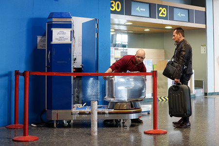 cling: VALENCIA, SPAIN - MAY 5, 2016: An airline passenger having his luggage wrapped in industrial strength cling film. Wrapping your luggage in industrial-strength cling film can provide peace of mind ahead of your journey. Editorial