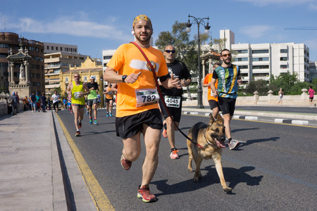 VALENCIA, SPAIN - MAY 15, 2016: A runner running with his dog at the Volta a Peu Valencia Caixa Popular 8k run. Over 15,000 runners competed in this run.