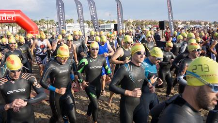 santander: VALENCIA, SPAIN - JUNE 4, 2016: Triathletes start the 1500 meter swim portion of the Santander Maritim Triathlon. The swim is followed by a 40 kilometer bike ride and then a 10 kilometer run. Editorial