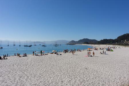 galicia: VIGO, SPAIN - AUGUST 18, 2016: Tourist on Rodas Beach on Cies Islands Natural Park off the coast of Vigo, Spain. With fine, white sand and crystal clear, emerald waters, Rodas Beach is half a mile long and 200 feet wide.