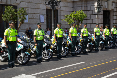VALENCIA, SPAIN - SEPTEMBER 1, 2016: Guardia Civil motorcycle officers standing at attention in front of the Valencia City Hall. The Guardia Civil was founded as a national police force in 1844.