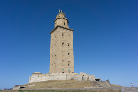 groyne: LA CORUNA, SPAIN - AUGUST 20, 2016: The Tower of Hercules with blue sky. The tower is the oldest Roman lighthouse in use today and overlooks the Atlantic coast of Spain from A Coruna.
