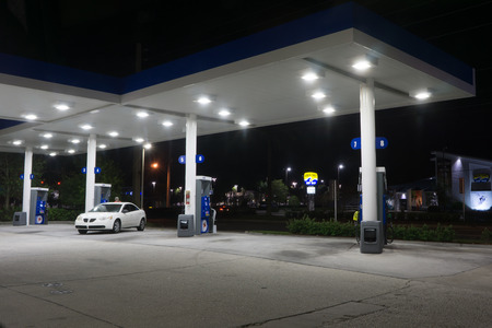 oil industry: JACKSONVILLE, FL-OCTOBER 16, 2016: A Exxon Mobil Gas Station at night. Exxon Mobil is the worlds 8th largest company by revenue and the fifth largest publicly traded company by market capitalization.