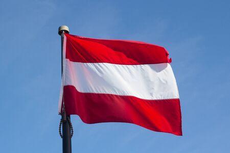 Flag of Austria Against a Windy Blue Sky Stok Fotoğraf