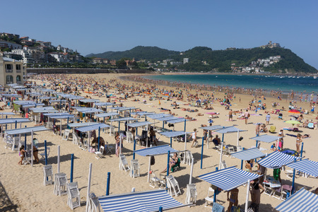 SAN SEBASTIAN, SPAIN - AUGUST 22, 2017: Unidentified people at the crowded Concha Beach. San Sebastian is one of the most famous tourist destinations in Spain. Redakční