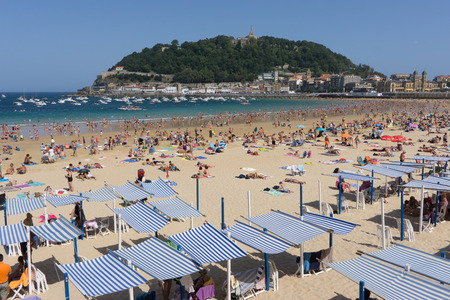 SAN SEBASTIAN, SPAIN - AUGUST 22, 2017: Unidentified people at the crowded Concha Beach. San Sebastian is one of the most famous tourist destinations in Spain. Editorial