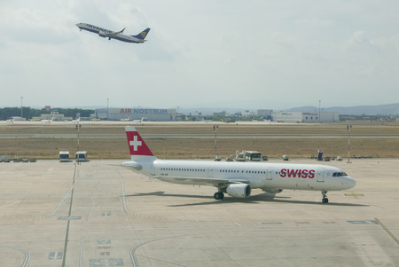 VALENCIA, SPAIN - SEPTEMBER 27, 2017: A Swiss Air Airliner taxing to the gate while a Ryan Air Airliner takes off in the background. Swiss Air is the national airline of Switzerland