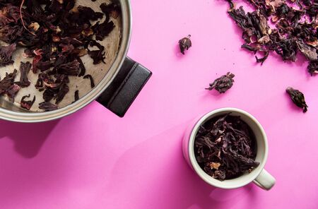 Hibiscus flower tea, also known as Agua de Jamaica, Roselle, sorrel and bissap. Dried hibiscus flowers in a pot, cup and loose on pink background. 版權商用圖片