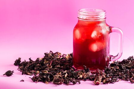Hibiscus flower tea, also known as Agua de Jamaica, Roselle, sorrel and bissap. Dried hibiscus flowers loose, surrounding a glass of iced hibiscus tea on pink background.