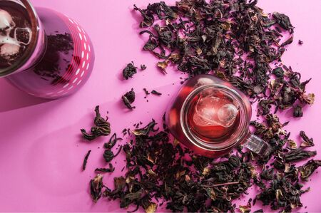 Hibiscus flower tea, also known as Agua de Jamaica, Roselle, sorrel and bissap. Dried hibiscus flowers loose on pink background with cool, iced hibiscus drink in jug and glass