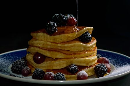 Stacked pancakes with summer berries and dripping honey maple syrup, isolated on black. Food, breakfast,snack. Copy space