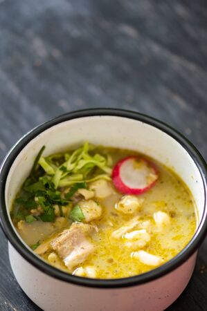 Pozole verde, or green posole is traditionally made with hominy and meat and topped with condiments. Mexican cuisine.