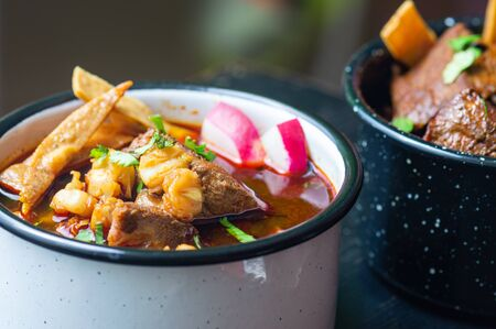 Mexican red pozole, hominy and pork stew, served with garnishes such as crispy tortillas, cilantro, lime and radish. Closeup. Фото со стока